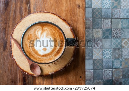 Cute Hot Latte Coffee on the wooden table over ceramic tile floor #293925074