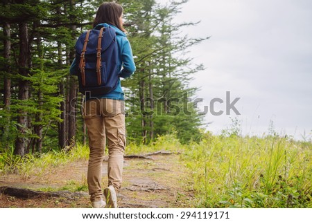 Hiker young woman with backpack walking on path in summer forest, rear view. Space for text in right part of image #294119171