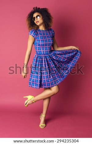 Young woman in fashionable dress and sunglasses on pink background. Afro hairstyle