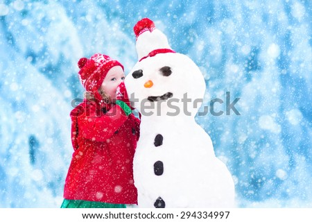 Funny little toddler girl in a red knitted Nordic hat and warm coat playing with a snow. Kids play outdoors in winter. Children having fun at Christmas time. Child building snowman at Xmas.