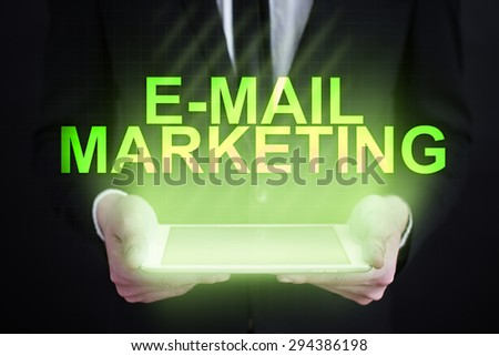 """Businessman holding a tablet pc with """"e-mail marketing"""" text on virtual screen. Internet concept. development."""