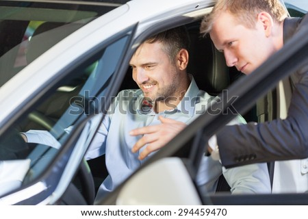 Client sitting in new car and talking with salesman #294459470