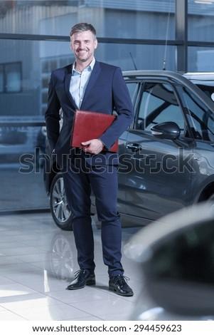 Smiling handsome salesman working in car showroom #294459623