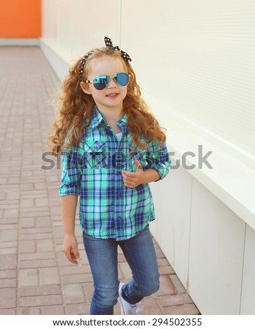 Fashion kid concept - stylish little girl child wearing a shirt and sunglasses posing outdoors in the city #294502355