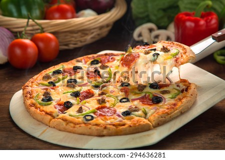 Delicious cheese stringy slice lifted of full supreme pizza baked fresh out of the oven next to ingredients #294636281