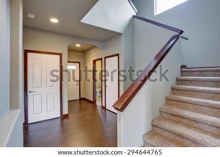 Elegant hallway with stairs, hardwood floor, and lovely dark wood trim. #294644765