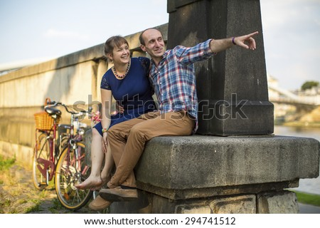 Happy young family. Couple in love sitting on the curb embankment and passionately talking. #294741512