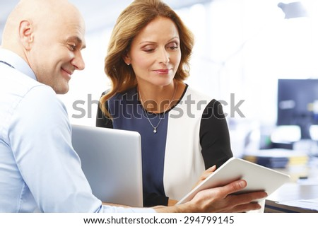 Senior businessman holding hands digital tablet and touch the screen. Businesswoman sitting  in font of computer and listening businessman.  #294799145