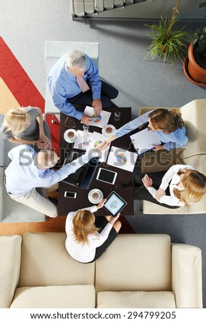 High angle view of business team sitting around the desk and shaking hands. Businesswomen and businessmen working with laptop and digital tablet while making business deal.  #294799205