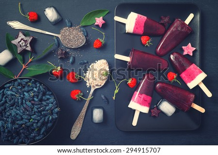 Homemade popsicles on black plate. Strawberry, honeysuckle berries, greek yogurt, oatmeal and chia seeds mix. #294915707