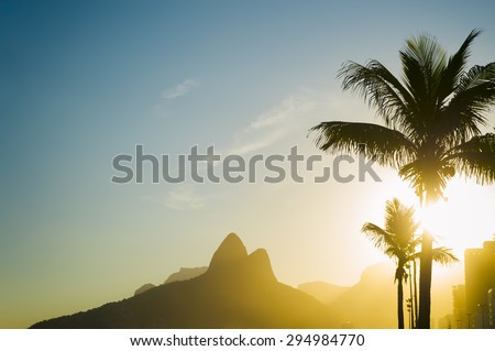 Sunset in Rio de Janeiro Ipanema Beach Brazil with Two Brothers Dois Irmaos Mountain and golden sun through palm trees silhouettes #294984770