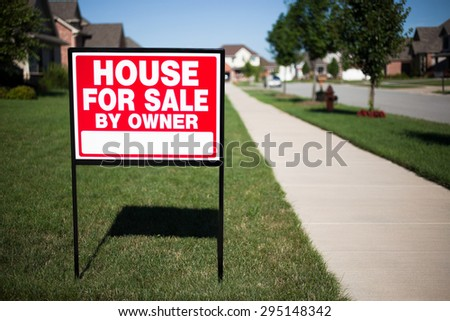 House For Sale By Owner Sign in a front yard of a home