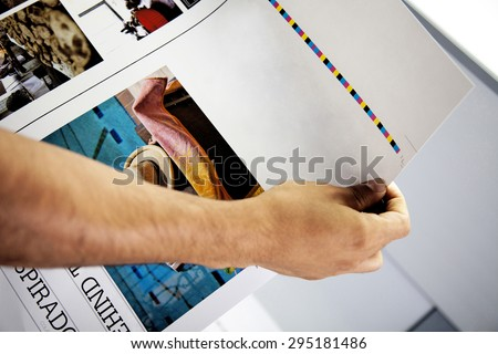 man's hand checking color proofs for printing, during production #295181486