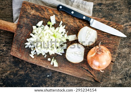 chopped onions on wooden cutting board, top view Royalty-Free Stock Photo #295234154