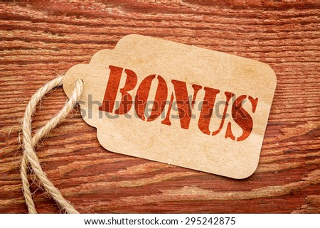 bonus sign a paper price tag against rustic red painted barn wood - shopping concept #295242875