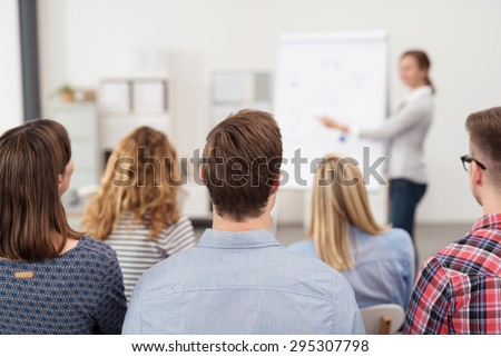 Rear View of Young Office Workers in Casual Outfits Listening to a Top Manager Explaining Something Using Illustrations. #295307798