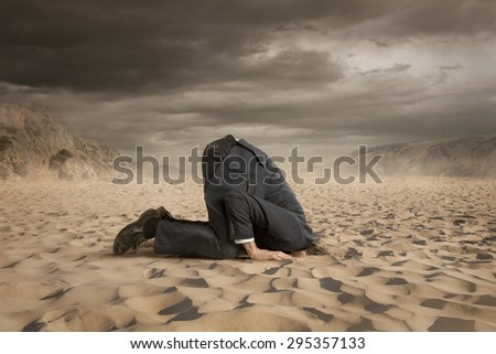 Young businessman hiding head in the sand Royalty-Free Stock Photo #295357133