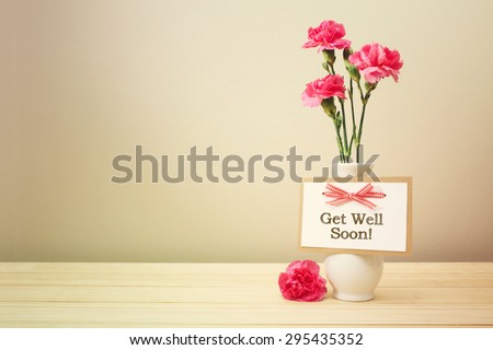 Get well soon message with pink carnations in a white vase #295435352