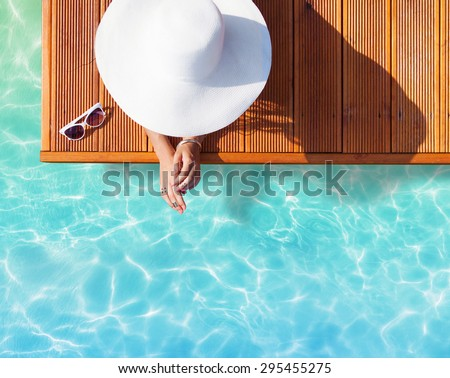 Summer holiday fashion concept - tanning woman wearing sun hat on a wooden pier view from above #295455275