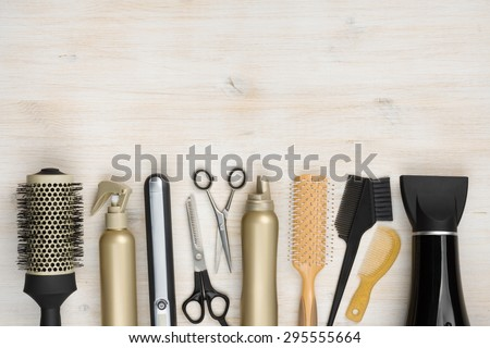 Hairdressing tools on wooden background with copy space at top Royalty-Free Stock Photo #295555664