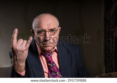 Elderly man making a horns gesture depicting heavy metal rock music or the sign of the devil, seated head and shoulders portrait on a dark background with copyspace Royalty-Free Stock Photo #295739888