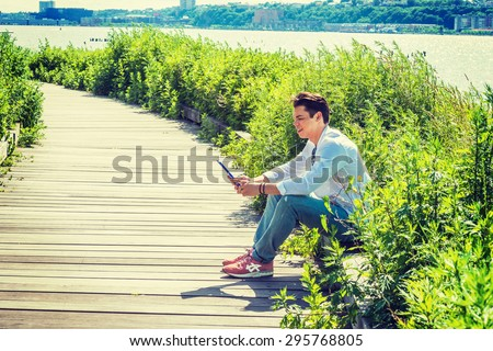 Modern Reading. Wearing white shirt, jeans, sneakers, sunglasses hanged on collar, a guy sitting on wooden road with grasses by Hudson River in New York, holding tablet computer, smiling, reading. #295768805