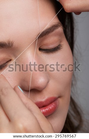 Close-up of female face during eyebrow correction procedure #295769567