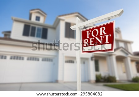 Red For Rent Real Estate Sign in Front of Beautiful House.