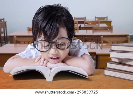 Cute girl wearing glasses and reading textbooks on the table in the classroom #295839725