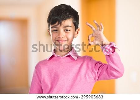 Child making Ok sign inside house #295905683