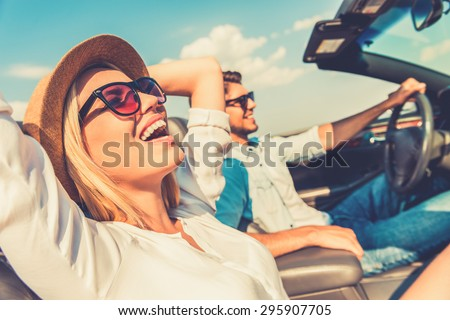 Freedom of the open road. Side view of joyful young woman relaxing on the front seat while her boyfriend sitting near and driving their convertible  Royalty-Free Stock Photo #295907705