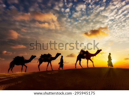 Travel background - two cameleers (camel drivers) with camels silhouettes in dunes of  desert on sunset Royalty-Free Stock Photo #295945175