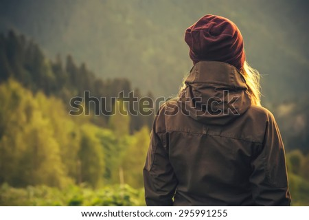 Young Woman standing alone outdoor with wild forest mountains on background Travel Lifestyle and survival concept rear view #295991255