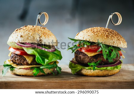 Delicious burgers with beef, tomato, cheese and lettuce #296090075
