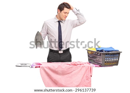 Studio shot of a confused young guy trying to iron his clothes isolated on white background