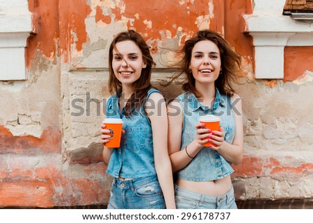 beautiful girls girlfriend drink delicious coffee and tea on the street in glasses smiling and having fun in denim #296178737