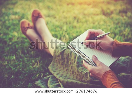 female hands with pen writing on notebook on grass outside #296194676