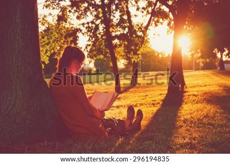 girl reading book at park in summer sunset light #296194835