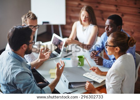 Group of multi-ethnic business partners discussing ideas Royalty-Free Stock Photo #296302733