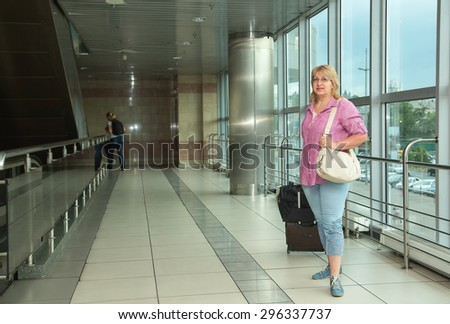 Adult woman is traveling. Woman with a suitcase goes on building the bus station, train station or airport. Retired woman embarks on a journey. Bags and suitcases for travel. Travel. Lifestyle. #296337737