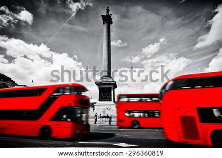 Red buses in motion on Trafalgar Square in London, UK. Nelson's column, black and white cloudy sky. #296360819
