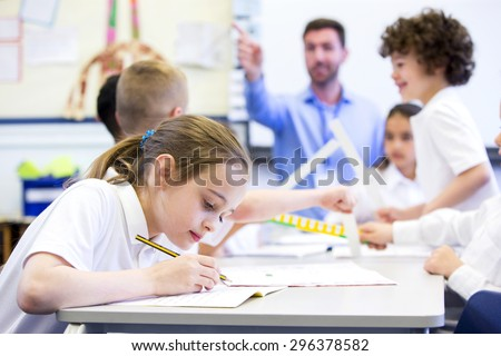 Schoolgirl sitting at a desk with other classmates while working. Her head is down while she concentrates. The teacher can be seen in the background.  #296378582