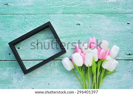 Tulip with blank picture frame on the wooden background.