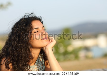 Woman relaxing and enjoying the sun in a warmth park at sunset Royalty-Free Stock Photo #296425169