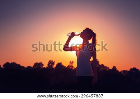 Silhouette of a girl at sunset with a bottle of water Royalty-Free Stock Photo #296457887