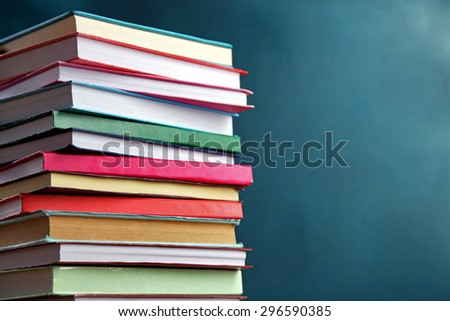 Stack of books on blackboard background #296590385