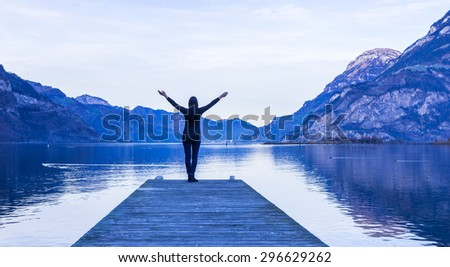 Epic landscape complete with a small woman figure. Mountain, lake and sky in bright colors of sunset