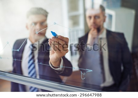 Businessman explaining graph to his colleague Royalty-Free Stock Photo #296647988