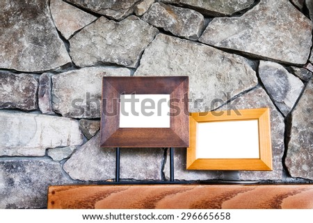 Two empty picture frames on a wooden shelf against an interior stone wall or fireplace. Customize with images or copy. Concept for invitation, announcement, message.