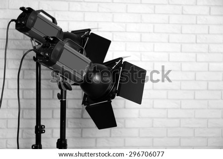 Photo studio with lighting equipment on brick wall background